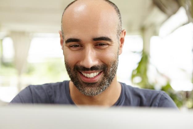 Personas y tecnología. primer plano de la cara feliz del atractivo hombre barbudo sentado frente a la pantalla del portátil y sonriendo con alegría mientras envía mensajes a amigos en línea a través de las redes sociales.