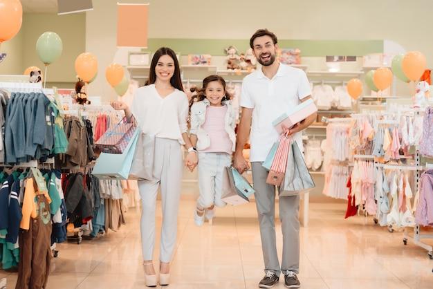 Personas en la tienda de ropa del centro comercial. la niña está saltando.