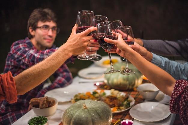 Personas tintineando vasos en la mesa