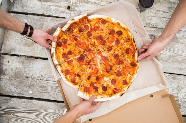 Personas tomando trozos de deliciosa pizza de caja.