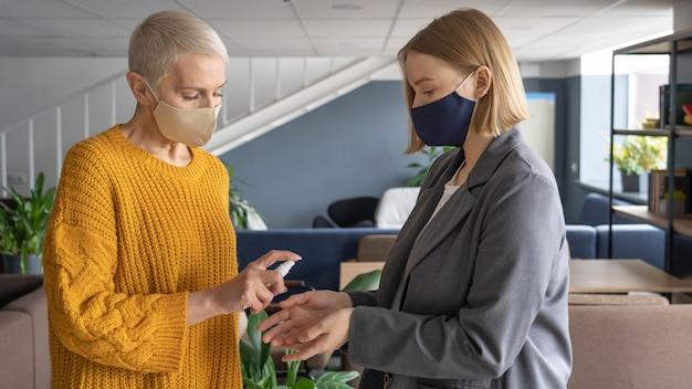 Personas en el trabajo con máscaras médicas.
