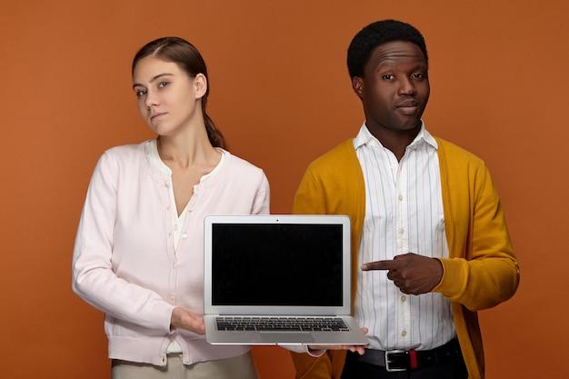Personas, trabajo, tecnología moderna y concepto de comunicación. exitosa joven y atractiva mujer europea y su elegante colega africano posando juntos, sosteniendo un portátil con pantalla negra