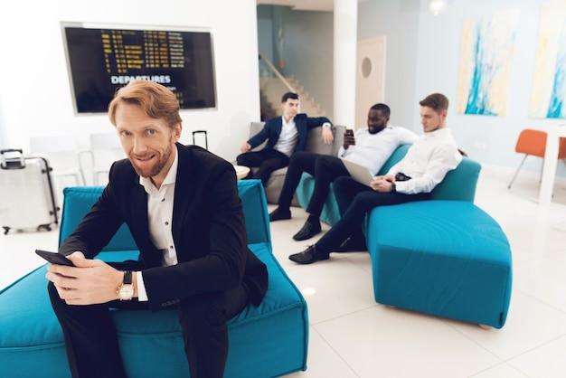 Personas en trajes están sentadas en la sala de espera del aeropuerto.