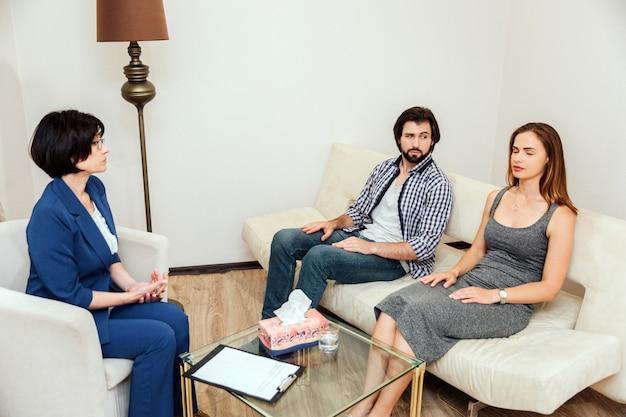 Las personas tranquilas y pacíficas están sentadas juntas con los ojos cerrados. están trabajando con psicólogo. el doctor está mirando a la pareja joven y hablando con ellos.