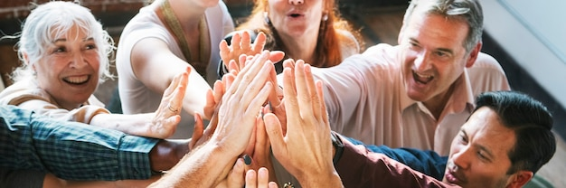 Personas uniendo sus manos en el aire.