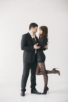 Personas vestidas con ropa clásica. pareja elegante en un momento sensual en la pared blanca.