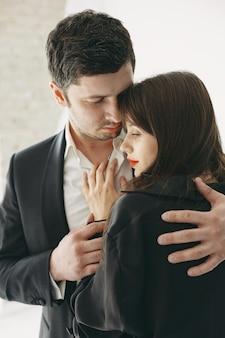 Personas vestidas con ropa clásica. pareja elegante en un momento sensual sobre fondo blanco.