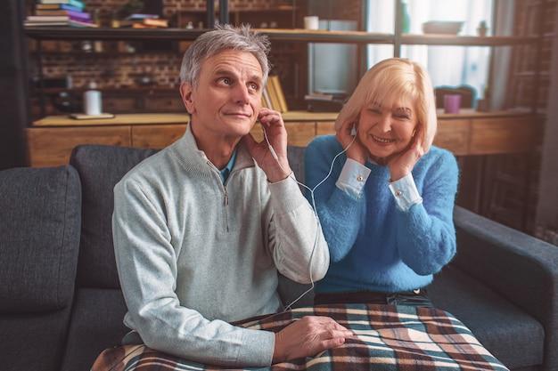 Las personas viejas pero hermosas escuchan música a través de la cabeza
