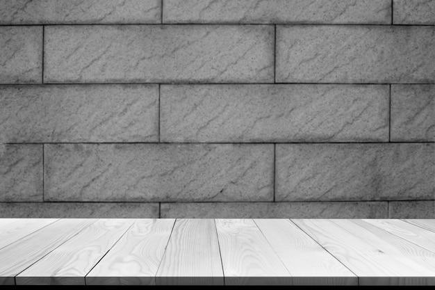 Perspectiva de madera mesa en blanco con estructura de grieta y áspero ladrillo gris viejo borroneada. mostrar textura vintage pared oscuro patrón sucio fondo de hormigón. sala de interiores. concepto de material de diseño.