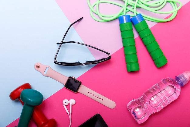 Pesas, cuerda para saltar, brazalete deportivo, agua y auriculares en color.