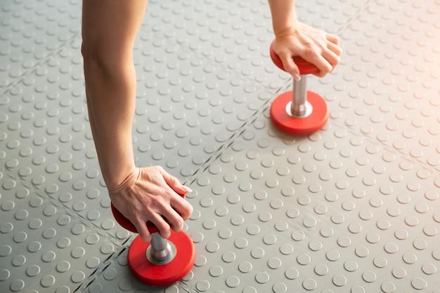 Pesas de ejercicio con mancuernas de pie en el suelo en el gimnasio
