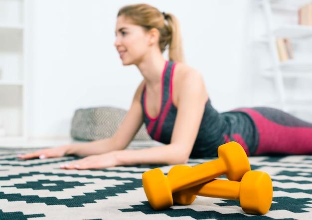 Pesas de gimnasia anaranjadas delante de la mujer joven de la aptitud que ejercita en la alfombra