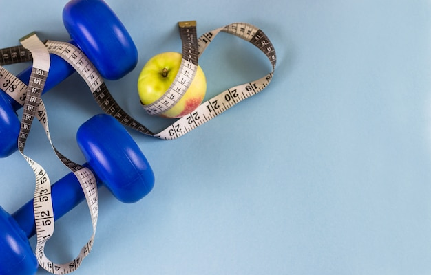 Pesas de gimnasia azules, cinta métrica y manzana en un fondo azul. se preocupa por el cuerpo.