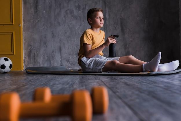 Pesas de gimnasia delante del muchacho que se sienta en la estera del ejercicio con la botella de agua