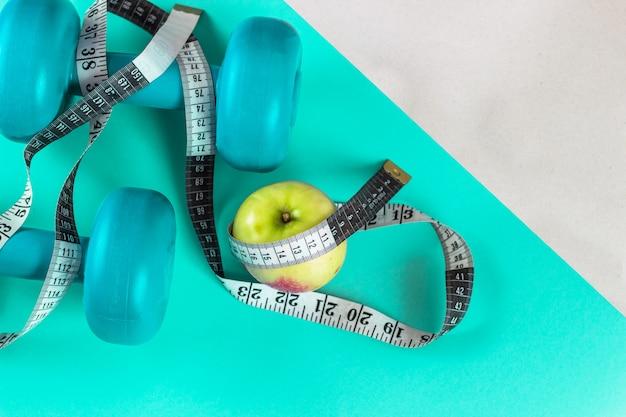 Pesas de gimnasia de la turquesa, cinta métrica y una manzana en un fondo brillante de la turquesa.