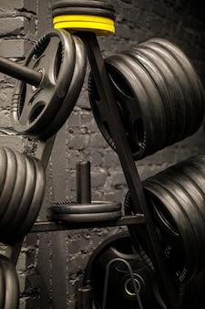 Pesas en un gimnasio de entrenamiento. interior de gimnasio cerca, maquinaria y equipo de levantamiento de pesas en estilo urbano moderno.