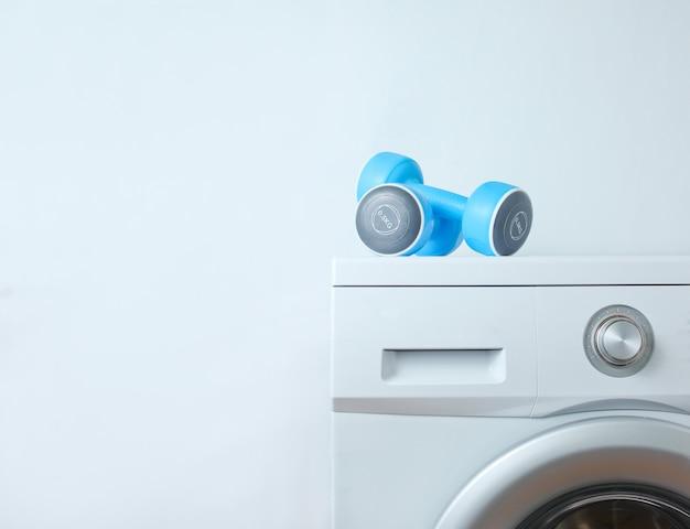 Pesas de plástico azul en la lavadora contra una superficie blanca