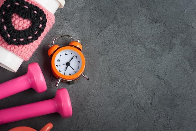 Pesas, taza de agua y reloj despertador