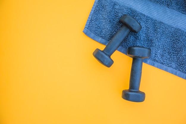 Pesas en la toalla sobre fondo amarillo