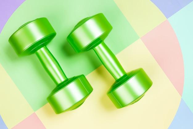 Pesas verdes sobre un fondo geométrico rosa, verde, amarillo aislado.