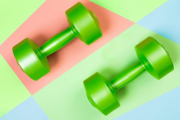 Pesas verdes sobre un fondo geométrico rosa, verde, azul aislado.