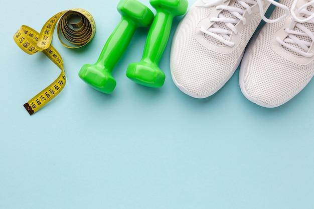 Pesas verdes zapatillas blancas y medidor
