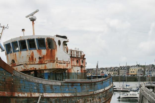 Pesca abandonada barco oxidado en la costa en el cielo nublado