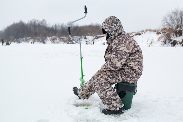 Pesca de invierno hiele la pesca del pescador en el invierno en el río.