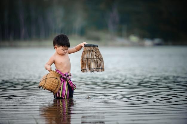 Pesca pesca niño en el río en el lado de país de thailandboy en el río en el lado de país de tailandia