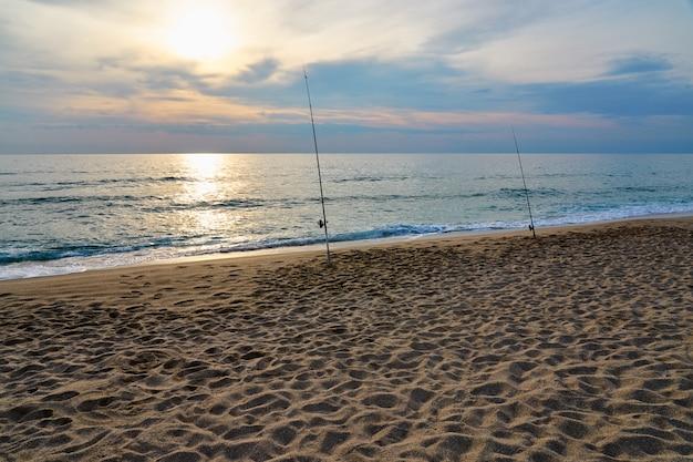Pesca en la playa de arena del mar en una puesta de sol.