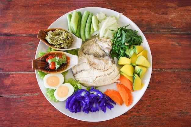 Pescado al vapor con salsa picante, huevos cocidos y verduras