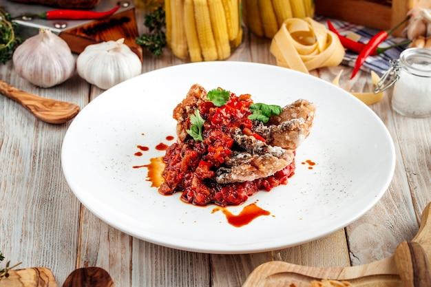 Pescado blanco frito con guiso de verduras en salsa roja sobre la mesa de madera