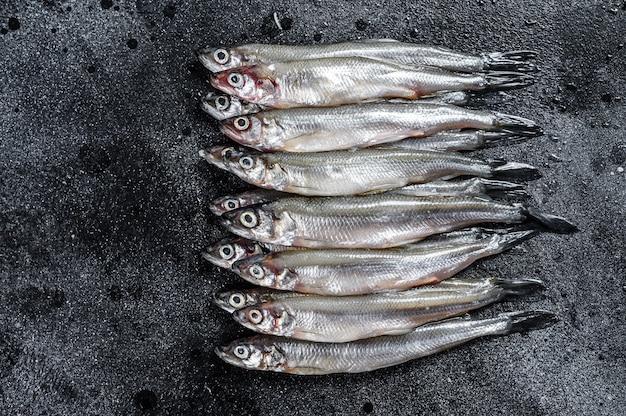 Pescado capelán fresco crudo. fondo negro. vista superior.