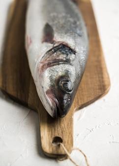 Pescado crudo de alto ángulo sobre tabla de madera