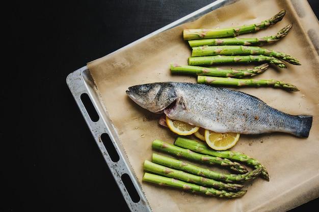 Pescado crudo con especias y verduras asparagarus en una bandeja para hornear listo para ser cocinado