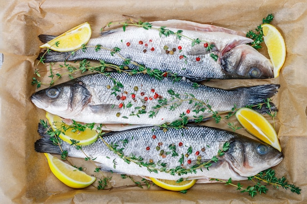 El pescado crudo fresco está listo para hornear con limón, tomillo, sal marina y pimienta rosa.