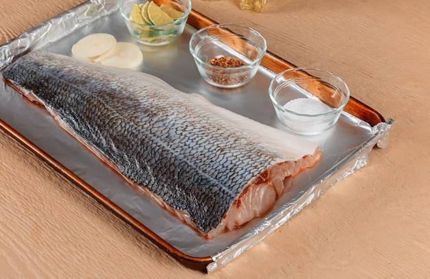Pescado crudo fresco preparado para hornear. marinado en especias de jugoso limón fresco