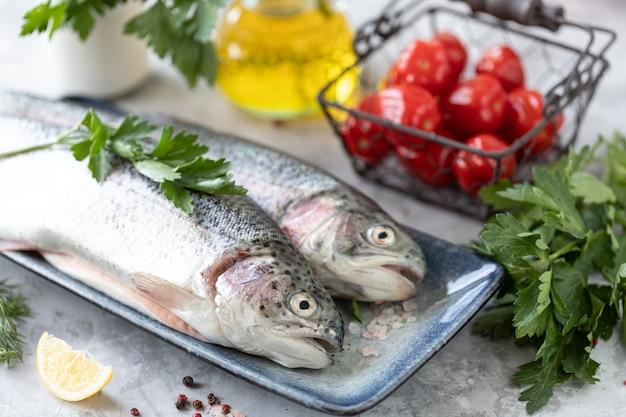Pescado crudo de trucha arco iris en un plato, verduras y verduras frescas para preparar alimentos sanos y sabrosos. dieta saludable y delicioso concepto culinario.