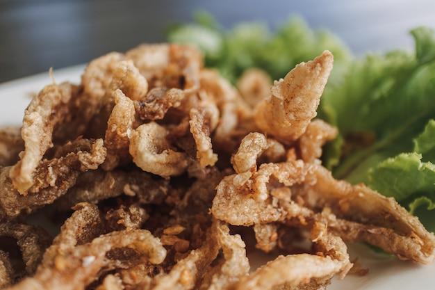 Pescado crujiente tailandés servido en plato blanco decorado con vegetales