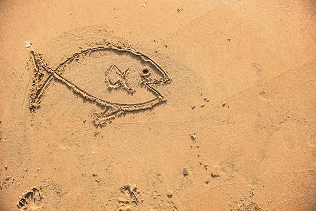 Pescado dibujado en la arena