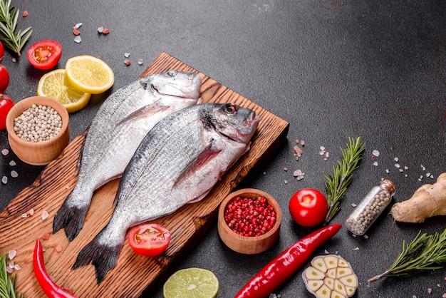 Pescado dorado crudo con especias cocinando en tabla de cortar. dorado de pescado fresco. dorado e ingredientes para cocinar en una mesa