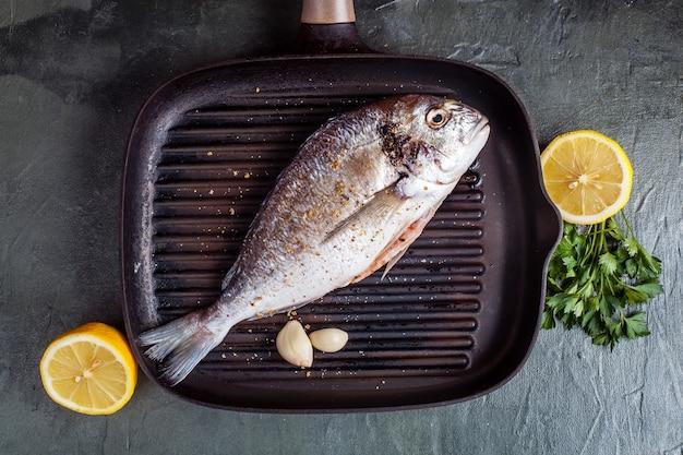 Pescado dorado crudo con especias y limón. vista superior