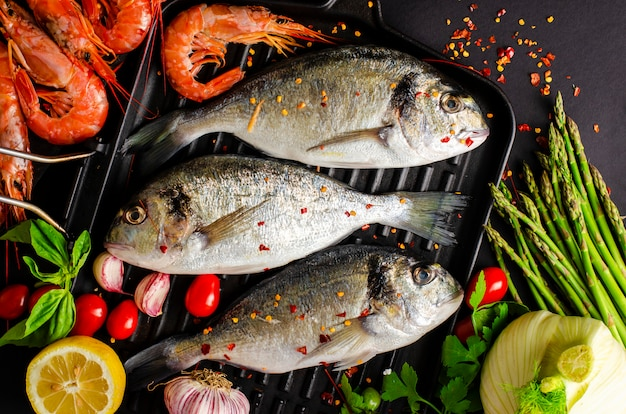 Pescado dorado fresco y langostinos tigre en una sartén de hierro y verduras para cocinar