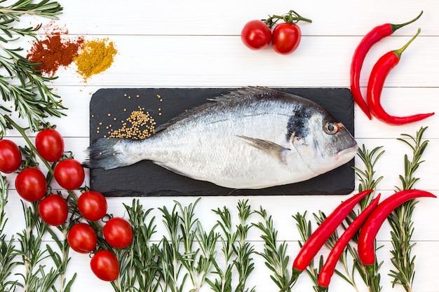 Pescado dorado fresco, romero, tomates cherry, pimienta fría en la mesa de madera blanca. vista superior.