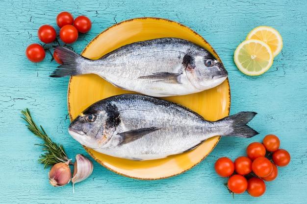 Pescado dorado en placa amarilla y verduras sobre fondo azul. vista superior.