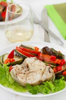 Pescado con ensalada y verduras y copa de vino blanco.