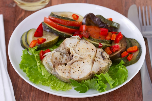 Pescado con ensalada y verduras en el plato.