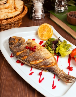 Pescado entero a la plancha con salsa amarilla, ensalada de verduras, limón y semillas de granada en un plato blanco