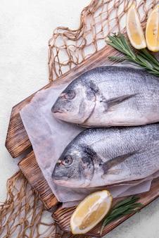 Pescado fresco besugo con rodajas de limón y red de pesca