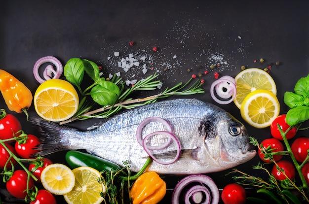 Pescado fresco crudo, dorado, dorada con limón, hierbas, verduras y especias